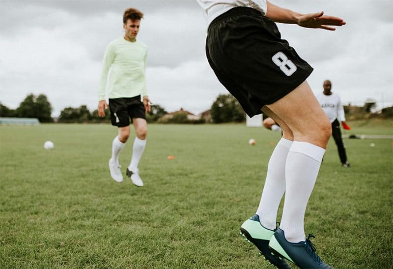 Soccer player on toes showing cleats socks shorts with player behhind