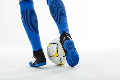 behind legs of a dribbling player