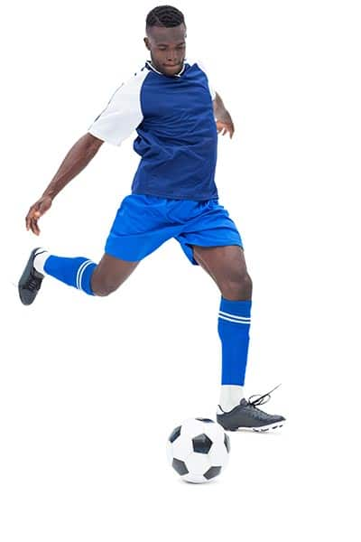 scocer player with leg swung to strike the ball