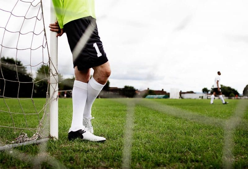 soccer player next to goal showing cleats socks shorts and jersey