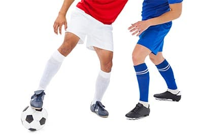soccer player with foot on the ball holding off an opponent
