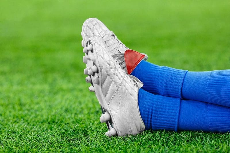 soccer players cleats and socks lying on grass - soccer compression socks