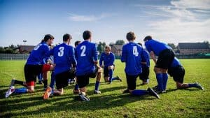 Soccer team on their knees on a field