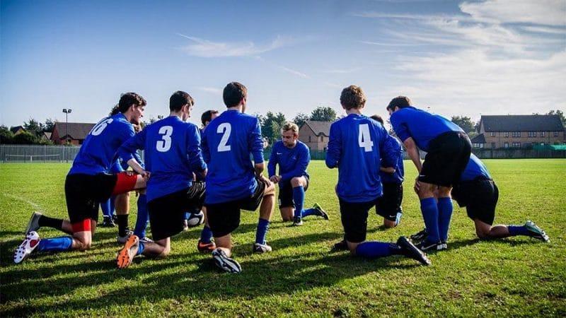 Soccer team on their knees on a field