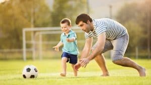 A 3-4-year-old kid playing soccer with dad, running after a ball